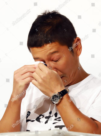Zozo founder Yusaku Maezawa wipes his tears as he announces Yahoo Japan will acquire Zozo at a press conference