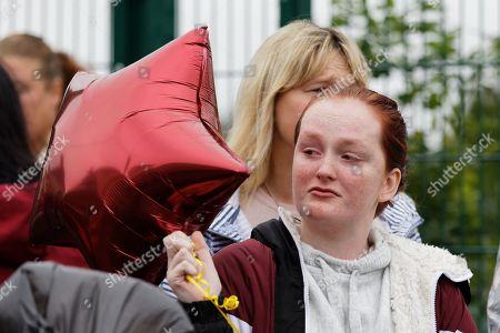 A young woman holds a balloon in memory of Bradley John outside St John Lloyd School, in Llanelli