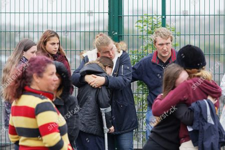Friends and family embrace each other outside St John Lloyd School, in Llanelli
