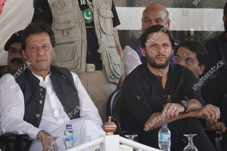 Pakistan's Prime Minister Imran Khan, left, attends a pro-Kashmir rally with former cricketer Shahid Afridi in Muzaffarabad, capital of Pakistani Kashmir, . Khan assured residents of disputed Kashmir on Friday that he will expose years-long Indian oppression and human rights violations in the region when he addresses the U.N. General Assembly this month