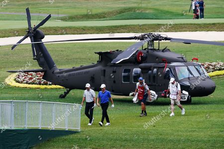 Mark Anderson, Doug Ghim. Golfers Mark Anderson, front left, and Doug Ghim, front right, walks past an Army helicopter on display during the second round of A Military Tribute at The Greenbrier golf tournament in White Sulphur Springs, W.Va