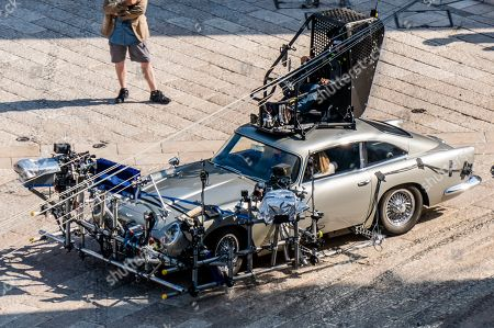 Stock Photo of Actor Daniel Craig is partially seen, left, sitting inside one of the Aston Martin DB5 used on the set of the latest James Bond movie 'No time to die' in Matera, southern Italy. The film is due out in spring 2020