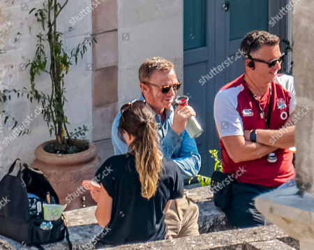 Stock Picture of Actor Daniel Craig, center, sips a drink during a break on the set of the latest James Bond movie 'No time to die' in Matera, southern Italy. The film is due out in spring 2020