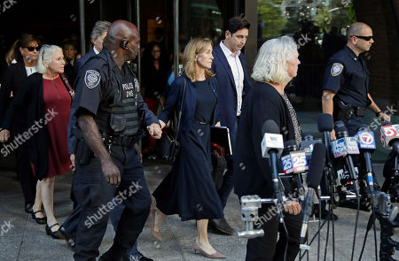 """Felicity Huffman, middle, leaves federal court after her sentencing in a nationwide college admissions bribery scandal, in Boston. """"Desperate Housewives"""" star Felicity Huffman was sentenced Friday to 14 days in prison for paying $15,000 to rig her daughter's SAT scores in the college admissions scandal that ensnared dozens of wealthy and well-connected parents"""