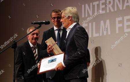 Stock Picture of Special guest Danish Academy Award-winning film and television director Bille August (R) receives the Lifetime Achievement Award of the 16th CineFest International Film Festival from Festival Director Tibor Biro (L) and Zoltan Alakszai registrar during its opening event in Miskolc, northeastern Hungary, 13 September 2019.