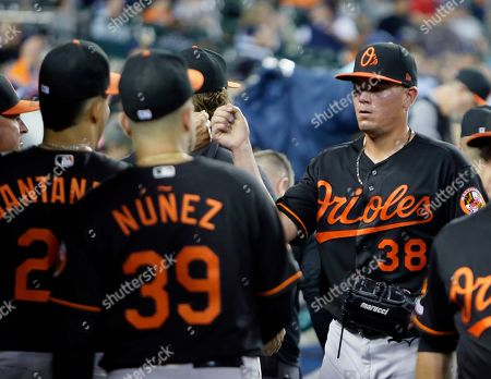 Baltimore Orioles starting pitcher Aaron Brooks is greeted by teammates after being pulled during the sixth inning of the team's baseball game against the Detroit Tigers, in Detroit. Brooks recorded his fifth win of the season in the Orioles' 6-2 victory