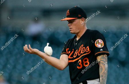 Baltimore Orioles' Aaron Brooks (38) uses a rosen bag during the first inning of a baseball game against the Detroit Tigers, in Detroit