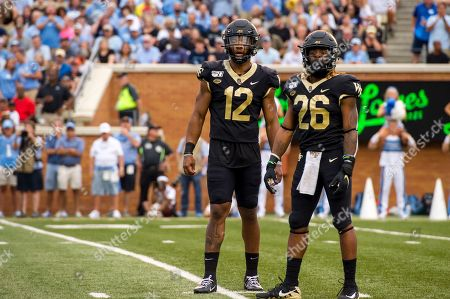 Wake Forest quarterback, Jamie Newman (12), and running back, Christian Beal-Smith (26), look to the sidelines for the play call during the first half