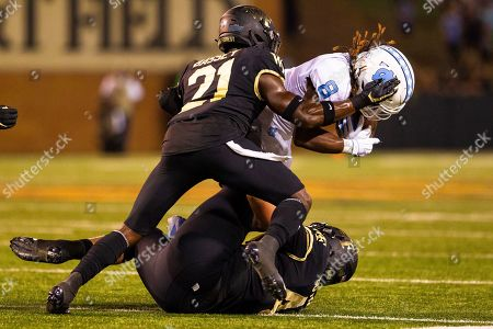 Wake Forest Demon Deacons defensive back Essang Bassey (21) and defensive back Amari Henderson (4) tackle North Carolina Tar Heels running back Michael Carter (8) for a loss in the third quarter of the NCAA matchup at BB&T Field in Winston-Salem, NC