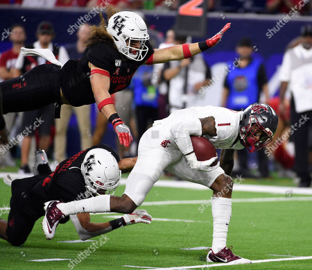 Washington State wide receiver Davontavean Martin (1) avoids the tackles of Houston safety Grant Stuard, top left, safety Gleson Sprewell during the second half of an NCAA college football game, in Houston