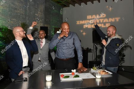 Sean Evans, right, hosts a hot pepper eating challenge with guests at Schick Xtreme: Baldest Party Ever during New York Fashion Week, in New York