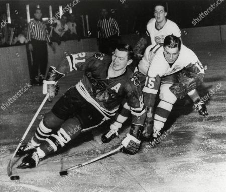 Chicago Blackhawks' Stan Mikita, left, pulls away from Detroit Red Wings' Ted Lindsay during an NHL hockey game in Chicago. A posthumous study of Mikita's brain shows the hockey Hall of Famer suffered from chronic traumatic encephalopathy at the time of his death a year ago. Dr. Ann McKee, the director of the BU CTE Center, announced the findings during the Concussion Legacy Foundation's Chicago Honors Dinner, at the request of Mikita's family