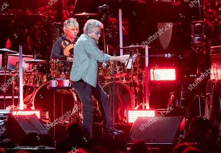 The Who's Roger Daltrey spins his microphone in front of drummer Zak Starkey at Fenway Park, in Boston