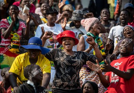 Members of the public sing as they gather in the stands for the funeral service of former president Robert Mugabe at the National Sports Stadium in the capital Harare, Zimbabwe . African heads of state and envoys are gathering to attend a state funeral for Mugabe, whose burial has been delayed for at least a month until a special mausoleum can be built for his remains
