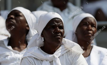Mourners attend the state funeral service for former President Robert Mugabe at the National Sports Stadium in Harare, . The burial has been delayed for at least a month until a special mausoleum can be built for his remains