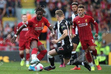 Liverpool forward Divock Origi (27) and Newcastle United defender Emil Krafth (17) during the Premier League match between Liverpool and Newcastle United at Anfield, Liverpool