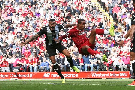 Liverpool defender Joel Matip (32) flies backward through the air but Referee Andre Marriner said no penalty during the Premier League match between Liverpool and Newcastle United at Anfield, Liverpool