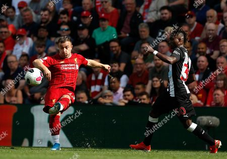 Newcastle's Christian Atsu, right, challenges Liverpool's Xherdan Shaqiri during the English Premier League soccer match between Liverpool and Newcastle at Anfield stadium in Liverpool, England