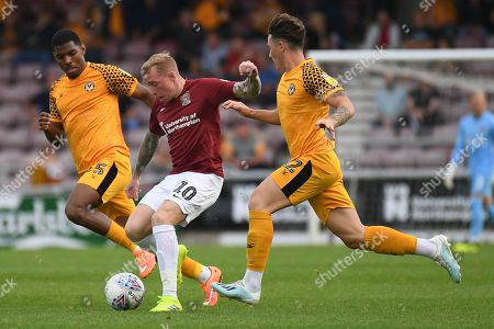 Northampton Town midfielder Nicky Adams (10) splits Newport County defender Kyle Hawkins (5) and Newport County defender (on loan from Millwall) Danny McNamara (12) during the EFL Sky Bet League 2 match between Northampton Town and Newport County at the PTS Academy Stadium, Northampton