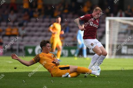 Newport County defender (on loan from Millwall) Danny McNamara (12) slides in to tackle Northampton Town midfielder Nicky Adams (10) during the EFL Sky Bet League 2 match between Northampton Town and Newport County at the PTS Academy Stadium, Northampton