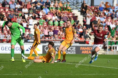 Stock Picture of Northampton Town defender midfielder Sam Hoskins (7) wheels away after scoring 2-0 while Newport County goalkeeper Tom King (1) shows his frustration during the EFL Sky Bet League 2 match between Northampton Town and Newport County at the PTS Academy Stadium, Northampton