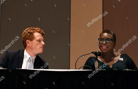 U.S. Rep. Joe Kennedy III, left, listens as Framingham Mayor Yvonne Spicer, right, speaks on a panel on race and politics, in Springfield, Mass