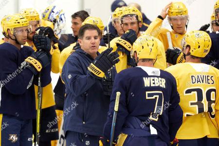 Nashville Predators head coach Peter Laviolette, center, speaks with players during NHL hockey training camp, in Nashville, Tenn