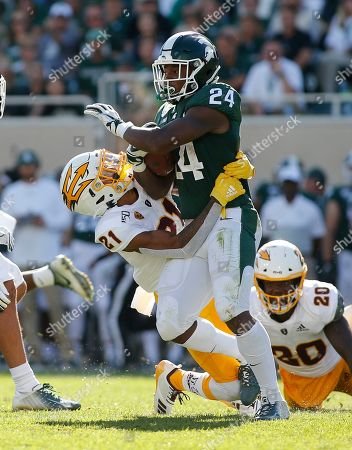 Michigan State's Elijah Collins (24) rushes against Arizona State's Jack Jones (21) during the first quarter of an NCAA college football game, in East Lansing, Mich