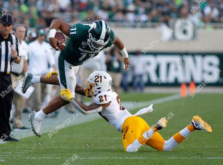 Michigan State's Connor Heyward, left, tries to avoid a tackle by Arizona State's Jack Jones (21) during the fourth quarter of an NCAA college football game, in East Lansing, Mich