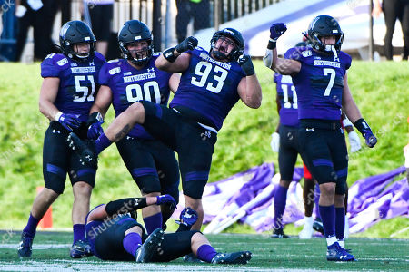 Stock Picture of Northwestern defensive lineman Joe Spivak (93) reacts with linebacker Blake Gallagher (51), defensive tackle Jake Saunders (90) and defensive back Travis Whillock (7) after he sacks UNLV quarterback Armani Rogers during the second half of an NCAA college football game, in Evanston, Ill