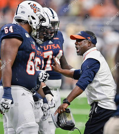 UTSA head coach Frank Wilson, right, talks to players, from left to right, Josh Dunlop Kevin Davis and Spencer Burford during the first half of an NCAA college football game against Army, in San Antonio