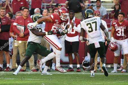 Arkansas tight end Cheyenne O'Grady slips past Colorado State defender Cam'ron Carter (12) and Logan Stewart (37) on his way to score a touchdown during the second half of an NCAA college football game, in Fayetteville, Ark