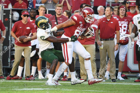 Stock Photo of Arkansas tight end Cheyenne O'Grady slips past Colorado State defender Cam'ron Carter on his way to score a touchdown during the second half of an NCAA college football game, in Fayetteville, Ark