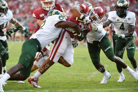 Arkansas running back Devwah Whaley pushes past Colorado State defender Cam'ron Carter (left) and Jalen Bates to score a touchdown during an NCAA college football game, in Fayetteville, Ark
