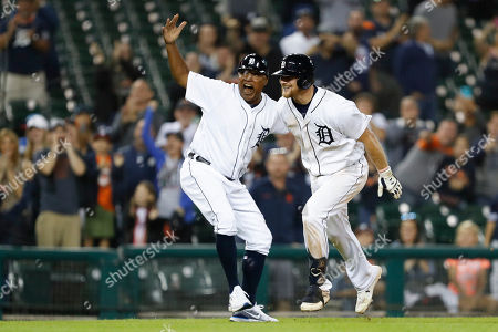 Detroit Tigers' John Hicks, right, celebrates with third base coach Dave Clark after hitting a grand slam against Baltimore Orioles' Ryan Eades during the 12th inning of a baseball game, in Detroit