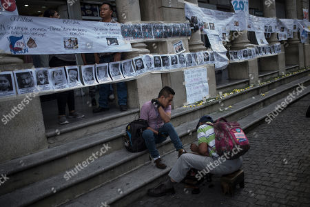 A man gets his shoes shined next to signs against Guatemalan President Jimmy Morales placed by protestors prior to independence day celebrations near the Constitution square in Guatemala City, . Guatemala and Central America celebrate 198 years of independence from Spain