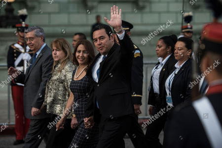 Guatemalan President Jimmy Morales waves to reporters accompanied by first lady Patricia Marroquin as they arrive to the National Palace for the independence day celebration in Guatemala City, . Guatemala and Central America are celebrating 198 years of independence from Spain