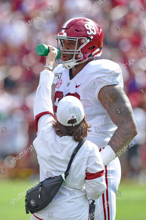 Alabama's Raekwon Davis (99) gets a drink of water from a trainer during the second half of an NCAA college football game against South Carolina, in Columbia, S.C