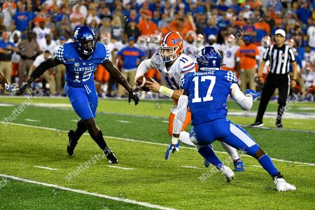 Stock Picture of Florida quarterback Kyle Trask (11) tries to avoid the defense of Kentucky linebacker Jordan Wright (15), and linebacker DeAndre Square (17) during the second half of an NCAA college football game in Lexington, Ky., . Florida won 29-21