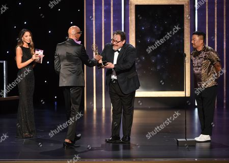 """RuPaul, left, accepts the award for outstanding host for a reality or competition program for """"RuPaul's Drag Race"""", from Jon Farvreau, center, and Roy Choi on night one of the Television Academy's 2019 Creative Arts Emmy Awards, at the Microsoft Theater in Los Angeles"""