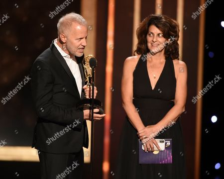 """Christopher Collins, Lydia Tenaglia. Christopher Collins, left, and Lydia Tenaglia accept the award for outstanding writing for a nonfiction program for """"Anthony Bourdain Parts Unknown: Kenya"""" on night one of the Television Academy's 2019 Creative Arts Emmy Awards, at the Microsoft Theater in Los Angeles"""