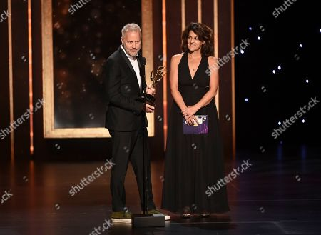 """Stock Photo of Christopher Collins, Lydia Tenaglia. Christopher Collins, left, and Lydia Tenaglia accept the award for outstanding writing for a nonfiction program for """"Anthony Bourdain Parts Unknown: Kenya"""" on night one of the Television Academy's 2019 Creative Arts Emmy Awards, at the Microsoft Theater in Los Angeles"""