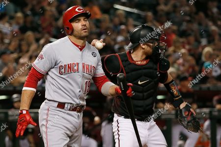 Cincinnati Reds' Joey Votto, left, closes his eyes after striking out as Arizona Diamondbacks catcher Carson Kelly, right, throws the ball to the infield during the ninth inning of a baseball game, in Phoenix. The Diamondbacks defeated the Reds 1-0