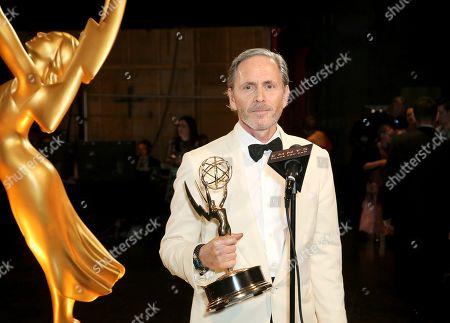 """Stock Picture of EXCLUSIVE - Keith Ian Raywood poses with the award for outstanding production design for variety, reality or competition series for """"Saturday Night Live Host: John Mulaney - Host: Emma Stone"""" during night one of the Television Academy's 2019 Creative Arts Emmy Awards, at the Microsoft Theater in Los Angeles"""