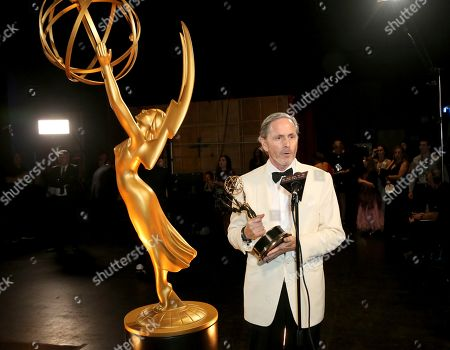 """EXCLUSIVE - Keith Ian Raywood poses with the award for outstanding production design for variety, reality or competition series for """"Saturday Night Live Host: John Mulaney - Host: Emma Stone"""" during night one of the Television Academy's 2019 Creative Arts Emmy Awards, at the Microsoft Theater in Los Angeles"""