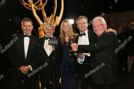 "Keith Scholey, right, and the team from of ""Our Planet"" pose backstage with the award for outstanding documentary or nonfiction series on night one of the Television Academy's 2019 Creative Arts Emmy Awards, at the Microsoft Theater in Los Angeles"