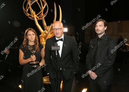 """Dan Reed, center, and the team from """"Leaving Neverland"""" pose backstage with the award for outstanding documentary or nonfiction special on night one of the Television Academy's 2019 Creative Arts Emmy Awards, at the Microsoft Theater in Los Angeles"""
