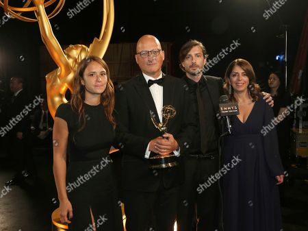 """Dan Reed, second from left, and the team from """"Leaving Neverland"""" pose backstage with the award for outstanding documentary or nonfiction special on night one of the Television Academy's 2019 Creative Arts Emmy Awards, at the Microsoft Theater in Los Angeles"""