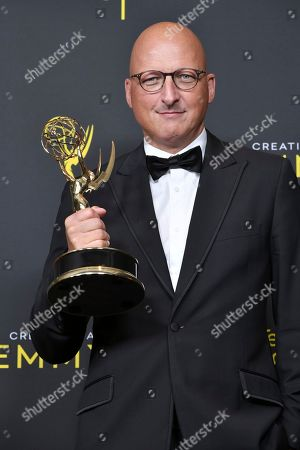 """Dan Reed poses in the press room with the award for outstanding documentary or nonfiction special for """"Leaving Neverland"""" on night one of the Creative Arts Emmy Awards, at the Microsoft Theater in Los Angeles"""