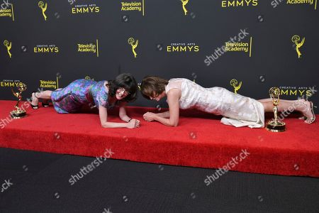 """Stock Image of Julie Cohen, Betsy West. Julie Cohen, left, and Betsy West pose in plank position in the press room with their awards for exceptional merit in documentary filmmaking for """"RBG"""" in the press room on night one of the Creative Arts Emmy Awards, at the Microsoft Theater in Los Angeles"""